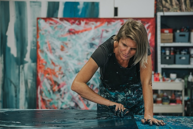 Young woman paints an abstract painting with her hands and spatula on a work table in her interior studio.