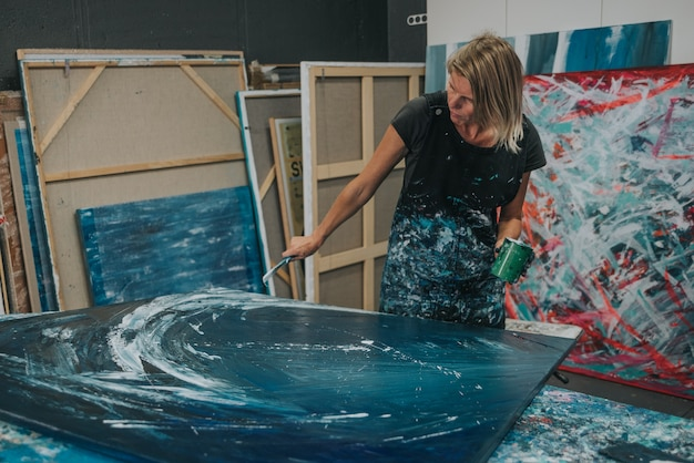 Young woman paints an abstract painting on a work table in her interior studio.