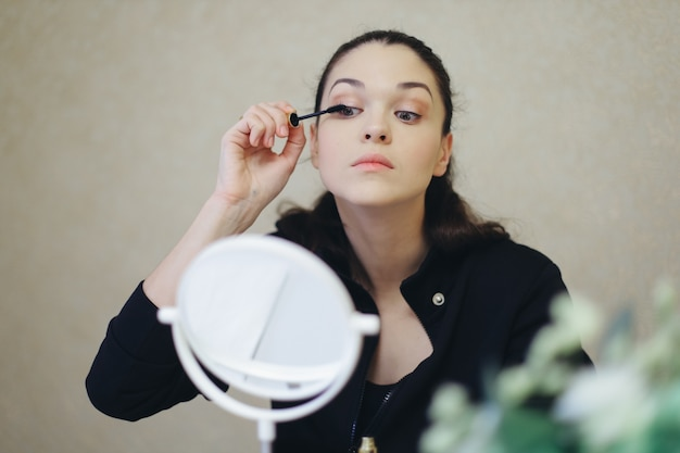 Young woman paints eyelashes with mascara in front of a mirror