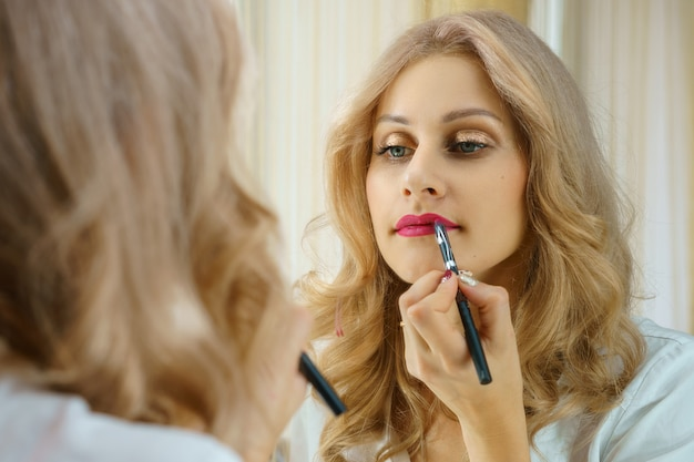 A young woman paints her lips at the mirror.