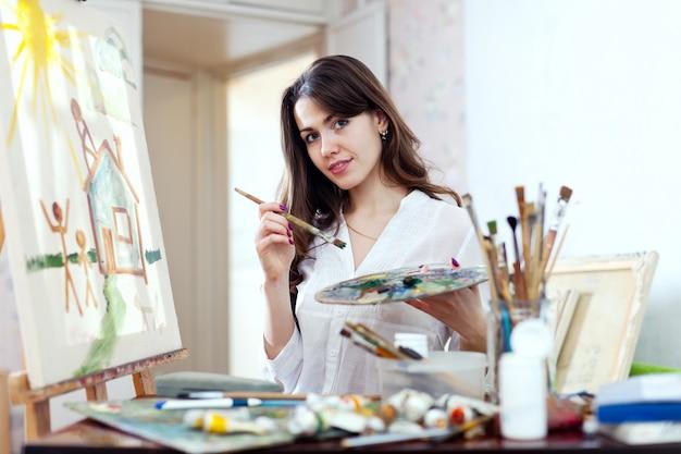 Молодая женщина рисует дом мечты