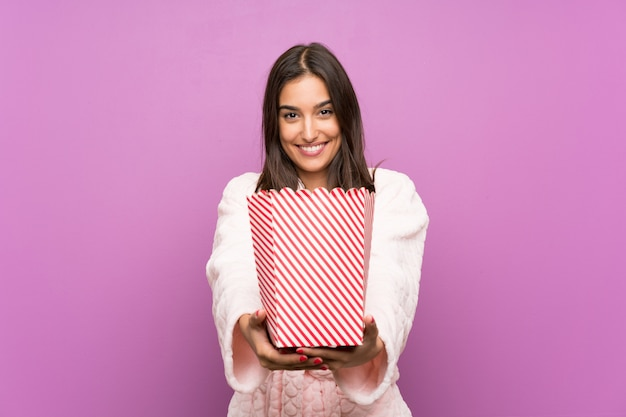 Young woman in pajamas and dressing gown over isolated purple background holding popcorns