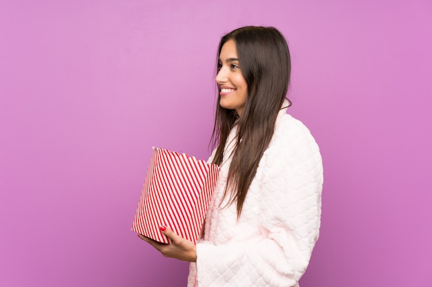 Young woman in pajamas and dressing gown over isolated purple wall holding popcorns