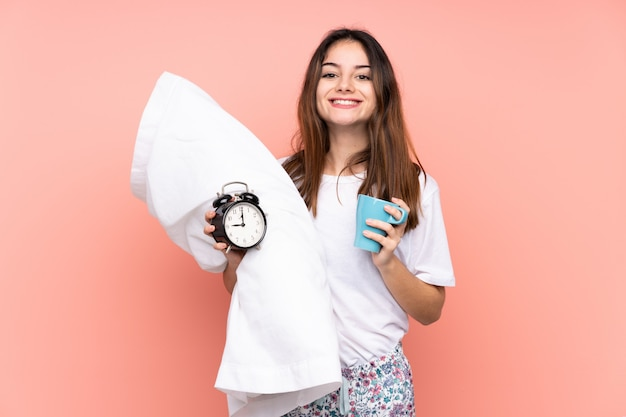 Young woman in pajamas and holding vintage clock isolated on pink wall