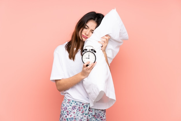 Young woman in pajamas and holding vintage clock isolated on pink