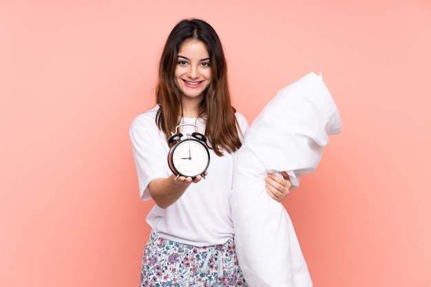Young woman in pajamas and holding vintage clock on pink wall