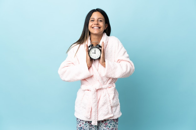 Young woman in pajamas over isolated in pajamas and holding clock with happy expression