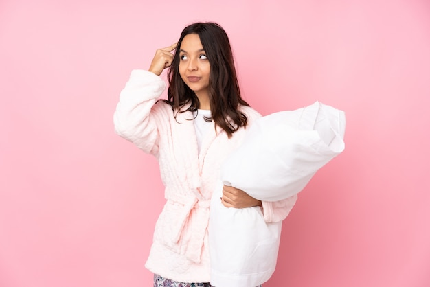 Young woman in pajamas isolated on pink wall having doubts and thinking