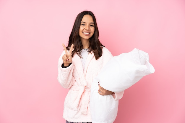 Young woman in pajamas isolated on pink wall smiling and showing victory sign