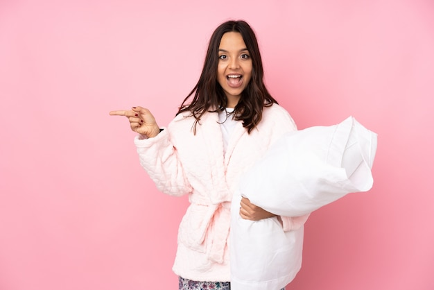 Young woman in pajamas isolated on pink wall surprised and pointing finger to the side