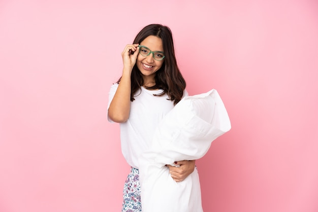Young woman in pajamas isolated on pink wall with glasses and happy