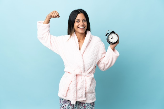 Young woman in pajamas over isolated wall in pajamas and holding clock while doing strong gesture