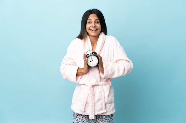 Young woman in pajamas over isolated wall in pajamas and holding clock with surprised expression