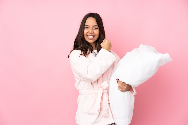 Young woman in pajamas on pink wall celebrating a victory