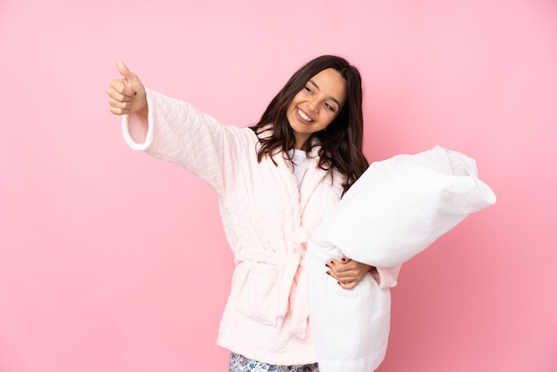 Young woman in pajamas on pink wall giving a thumbs up gesture