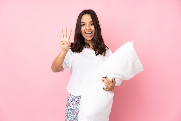 Young woman in pajamas on pink wall happy and counting four with fingers