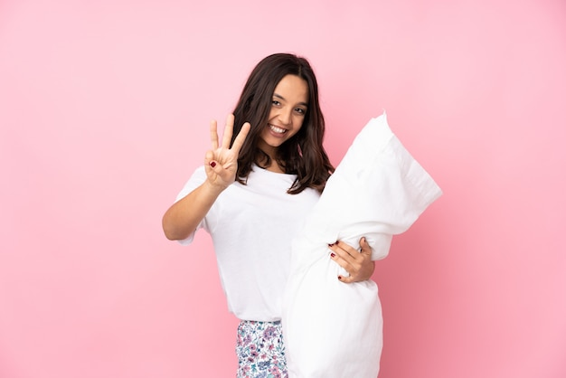 Young woman in pajamas on pink wall happy and counting three with fingers