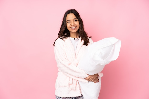 Young woman in pajamas on pink wall keeping the arms crossed in frontal position