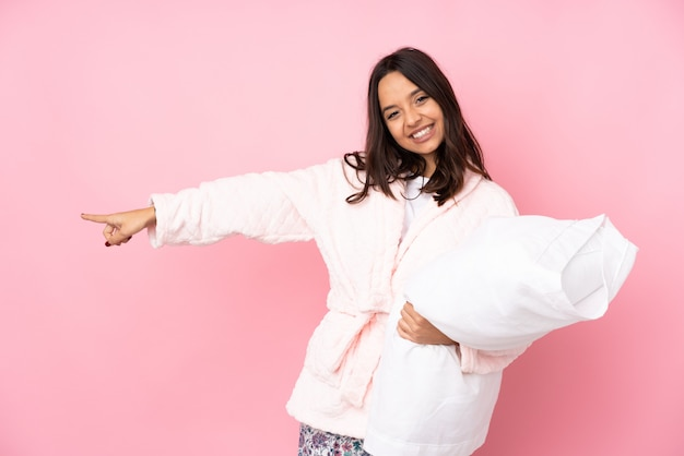 Young woman in pajamas on pink wall pointing finger to the side