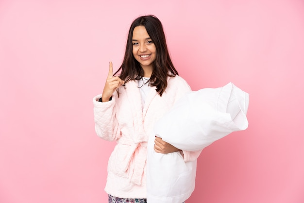 Young woman in pajamas on pink wall pointing up a great idea