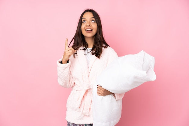 Young woman in pajamas on pink wall pointing up and surprised