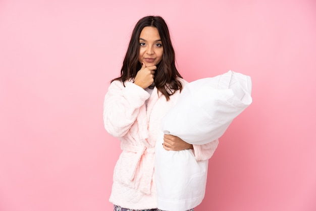Young woman in pajamas on pink wall thinking