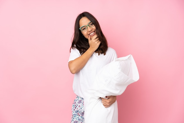 Young woman in pajamas on pink wall with glasses and smiling