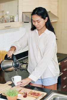 Young woman in pajamas pouring hot water in tea cup when making herself breakfast in kitchen