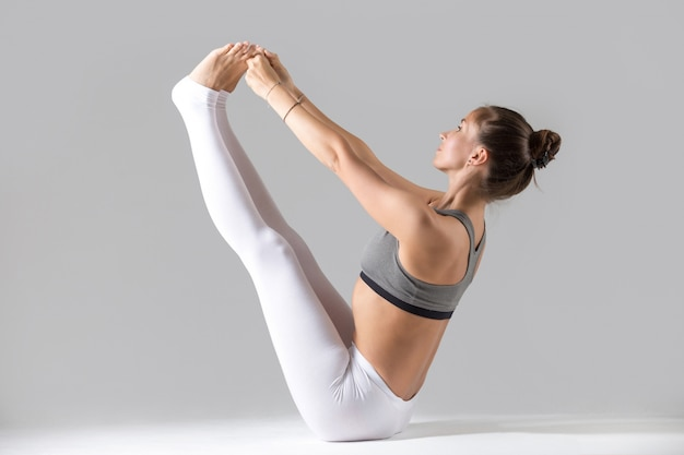 Young woman in paripurna navasana pose, grey studio background