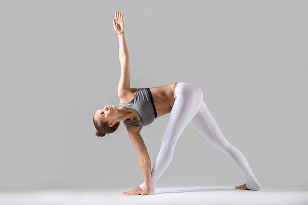 Young woman in parivrrta trikonasana pose, grey studio background