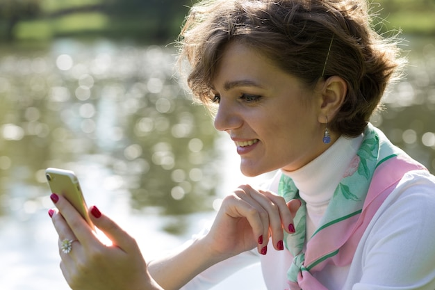 Young woman in the park speaks by mobile phone. cute girl portrait in french style.