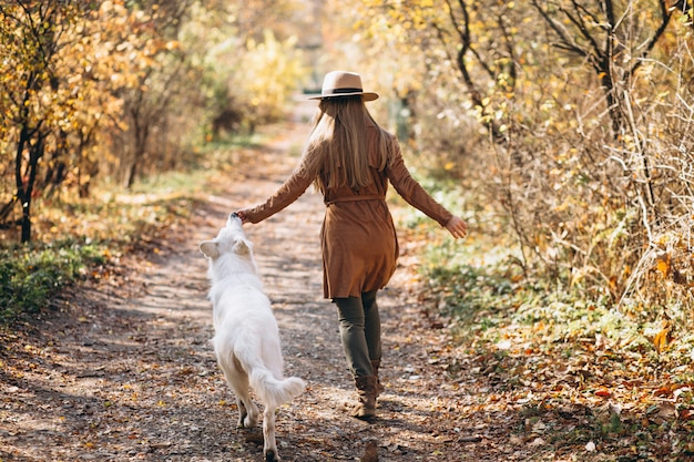 Young woman in park with her white dog