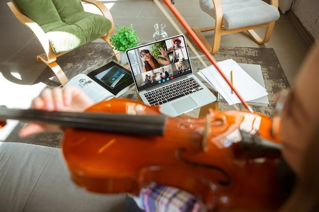 Молодая женщина участвует в видеоконференции, глядя на экран ноутбука во время виртуальной встречи, приложение веб-камеры видеозвонка для бизнеса, крупным планом. удаленная работа, фриланс, образование, концепция образа жизни.