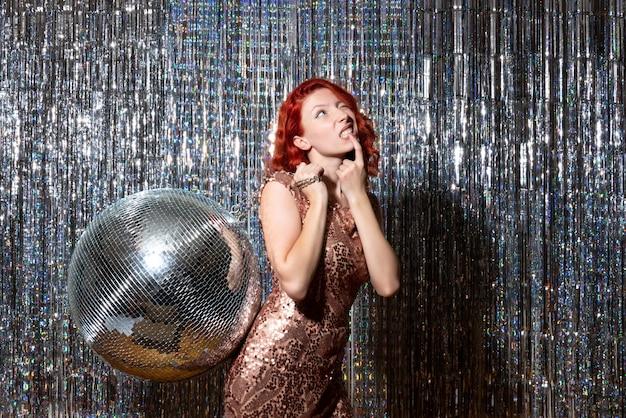 Giovane donna in festa con palla da discoteca su tende tende luminose