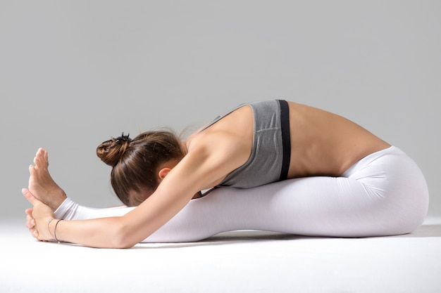 Young woman in paschimottanasana pose, grey studio background