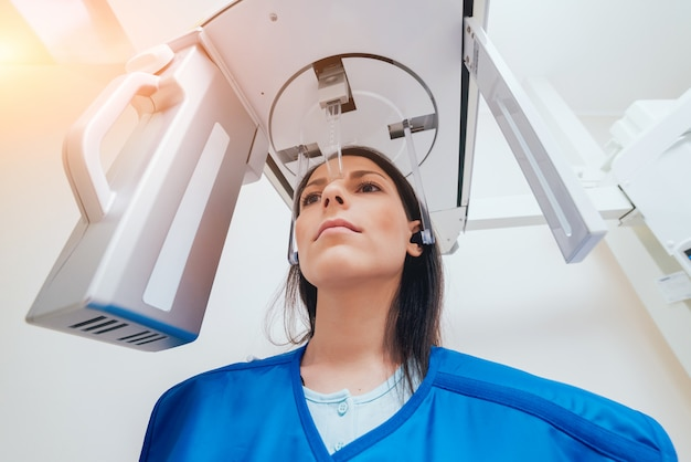 Young woman patient standing in x-ray machine.