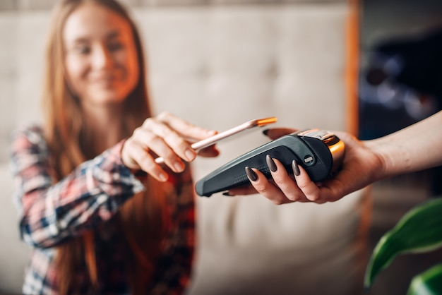 若い女性はカフェで携帯電話で支払います。現代の決済テクノロジー
