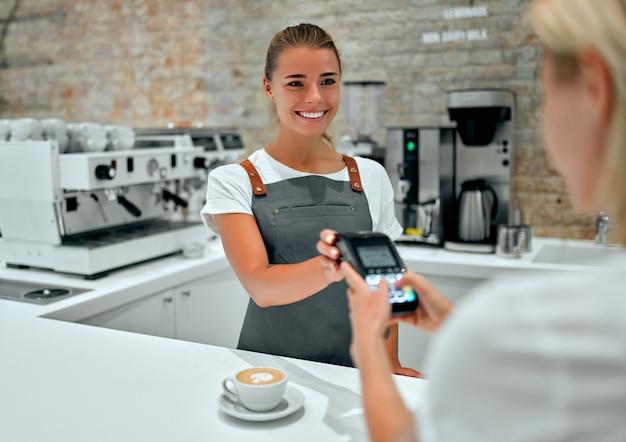 カフェでクレジットカードで支払う若い女性。コーヒーショップの女性バリスタチェックアウトカウンターでクレジットカードリーダーのセキュリティピンに入る女性。