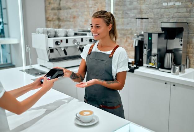 カフェでクレジットカードで支払う若い女性。コーヒーショップのチェックアウトカウンターの後ろに立っている女性のバリスタとクレジットカードリーダーのセキュリティピンに入る女性。