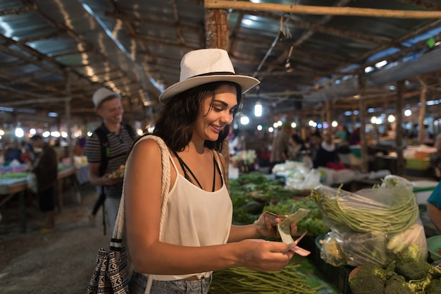 Young woman paying money for fresh vegetables on market girl shopping on street bazaar