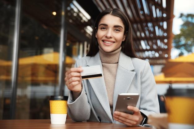 Молодая женщина платит онлайн, используя кредитную карту и мобильный телефон, сидя в кафе