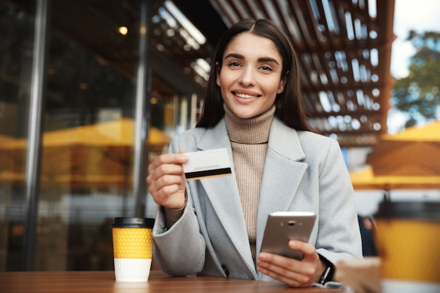 Young woman paying online, using credit card and mobile phone while sitting in a coffee shop
