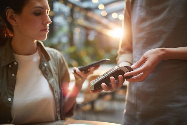 Молодая женщина расплачивается через смартфон в кафе