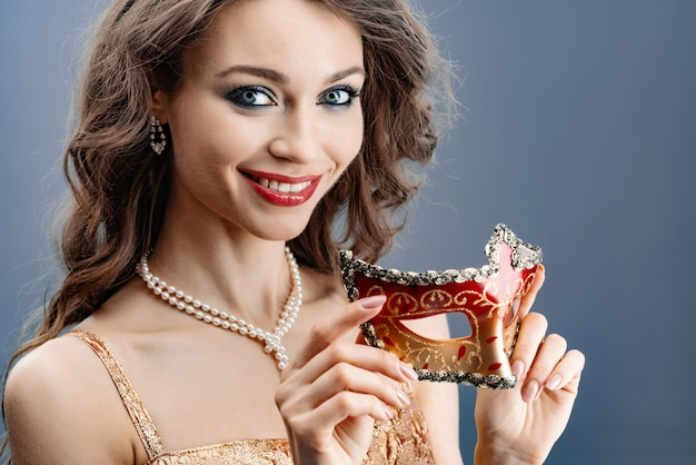 Young woman in a pearl necklace smiles holds a carnival mask in her hand close-up