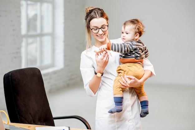 白いオフィスのインテリアで男の子と一緒に立っている医療用ガウンの若い女性小児科医