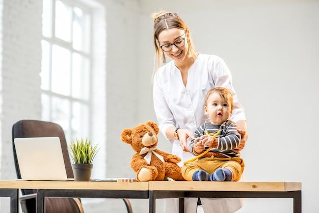 オフィスのテーブルに座っている男の子の世話をしている若い女性の小児科医