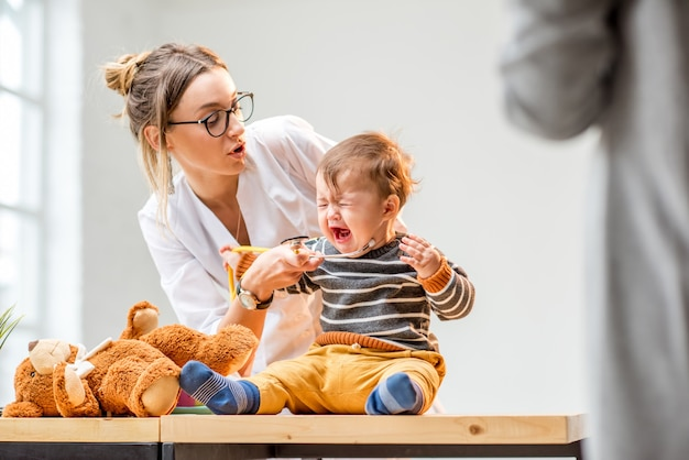 사무실에서 테이블에 앉아 아기를 돌보는 젊은 여자 소아과 의사
