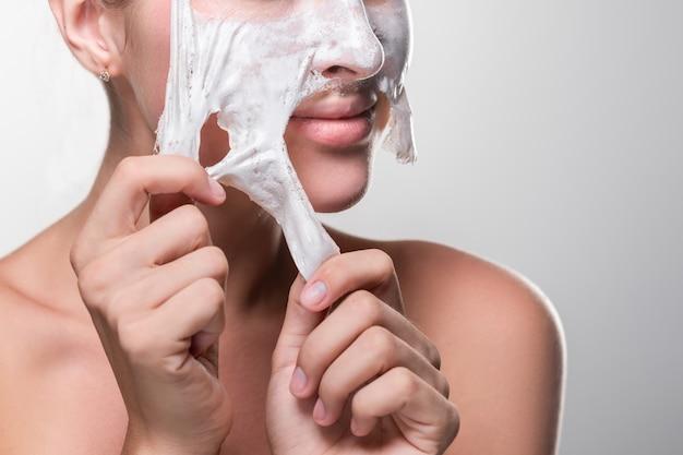 Young woman peeling off a facial mask