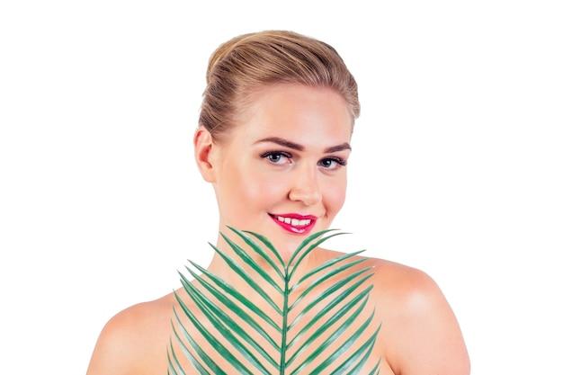 長いまつげと赤い口紅がトロピカルなヤシの葉のクローズアップを保持している若い女性の完璧な肌のメイクは、スタジオで裸の白い背景を肩に乗せます。