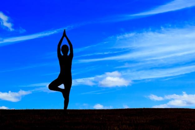 Молодая женщина выполняет йогу на скале в утреннем солнечном свете